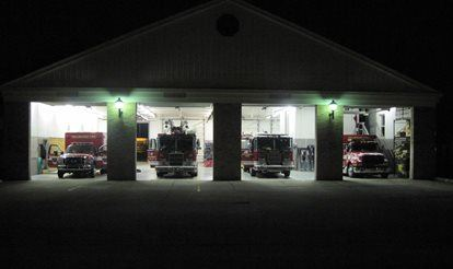 Emergency response vehicles like fire trucks and ambulances parked in their bays at the fire house.