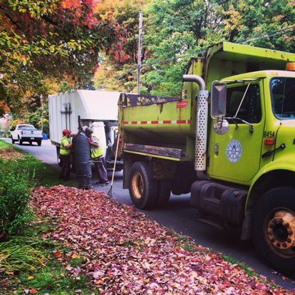 City Street Department workers collecting leaves in large industrial trucks